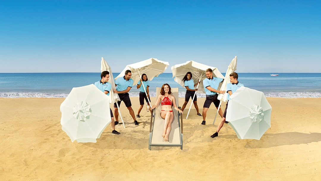 Lady on the beach surrounded by TUI staff