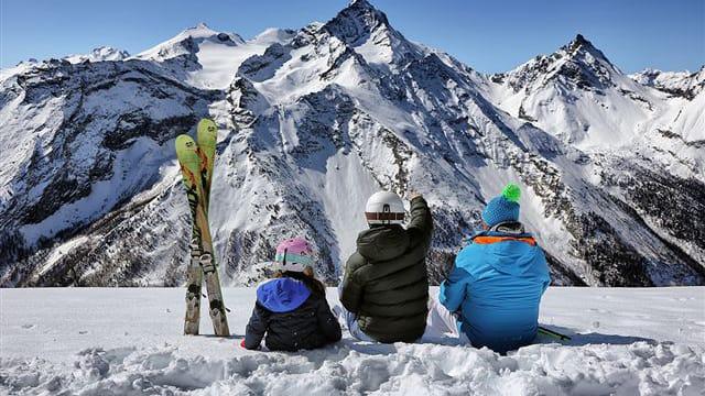 Skiers sitting on slipes in Pila