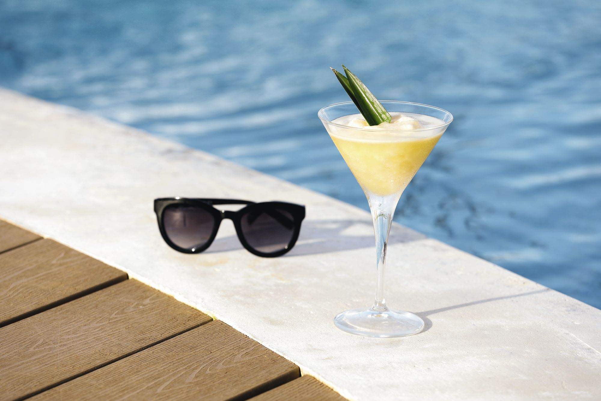 sunglasses and cocktail by pool