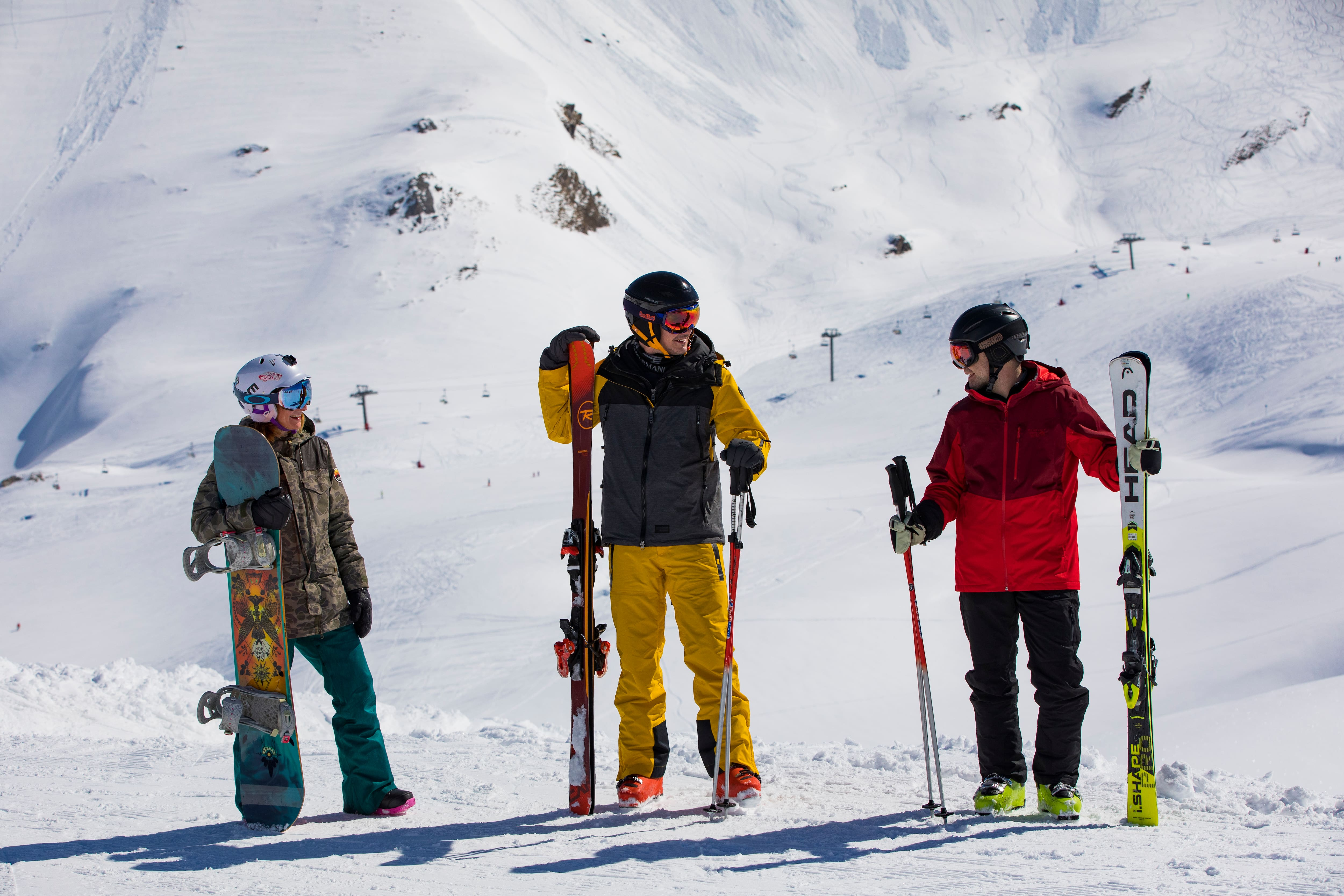 Two skiers and a snowboarder on the slopes