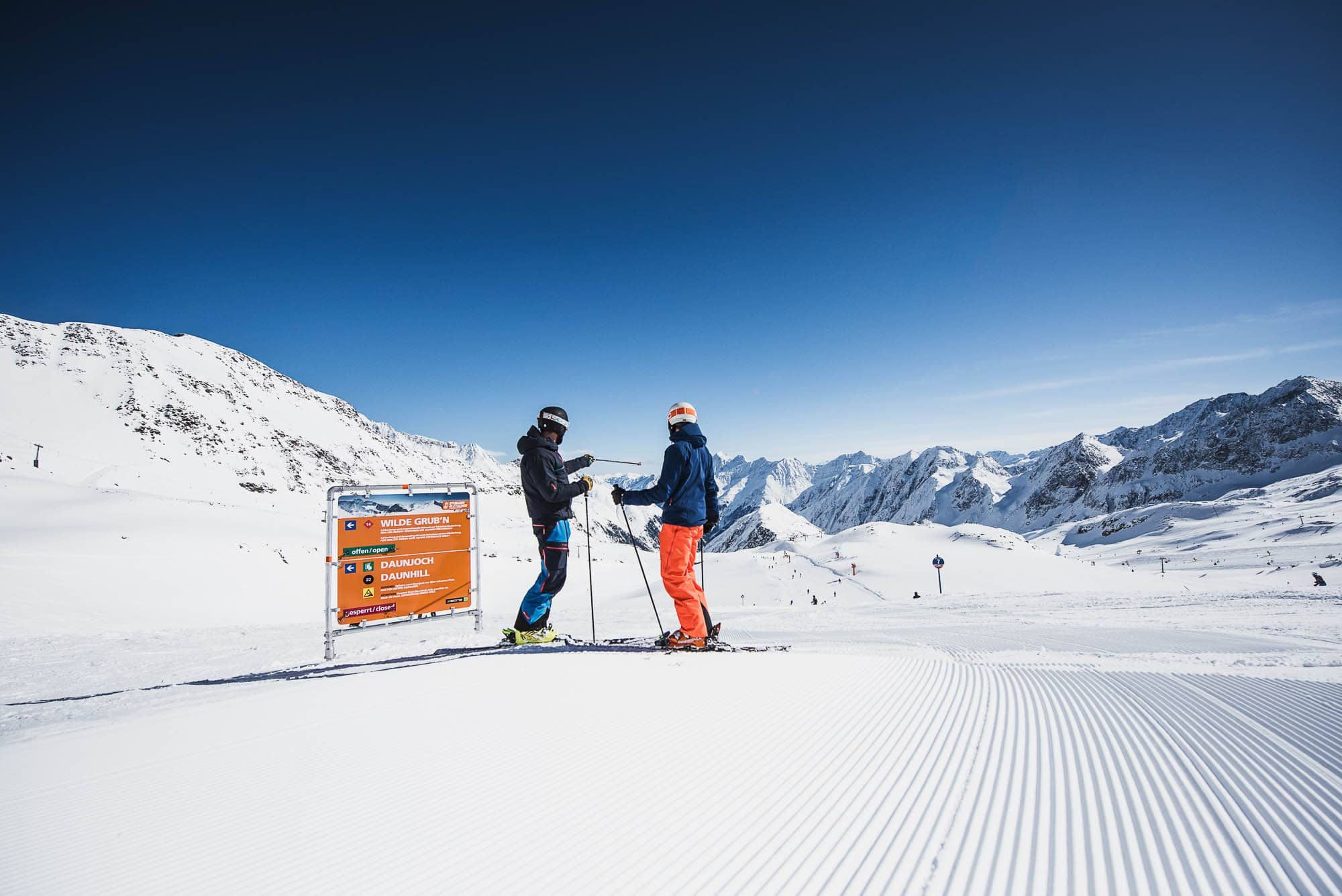 2 skiers standing on the piste