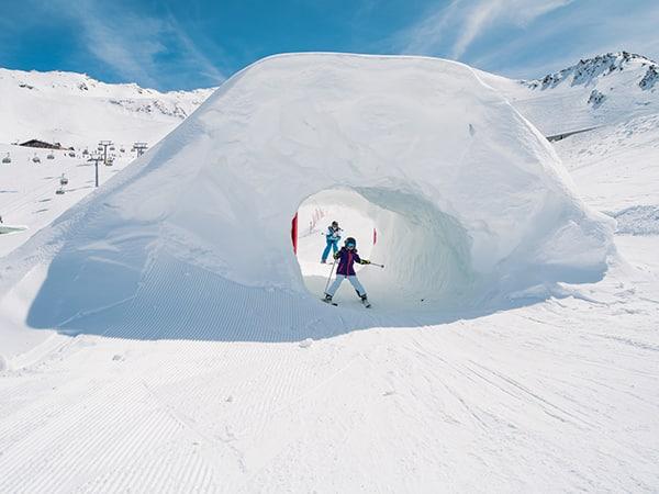 child skiing through a tunenel