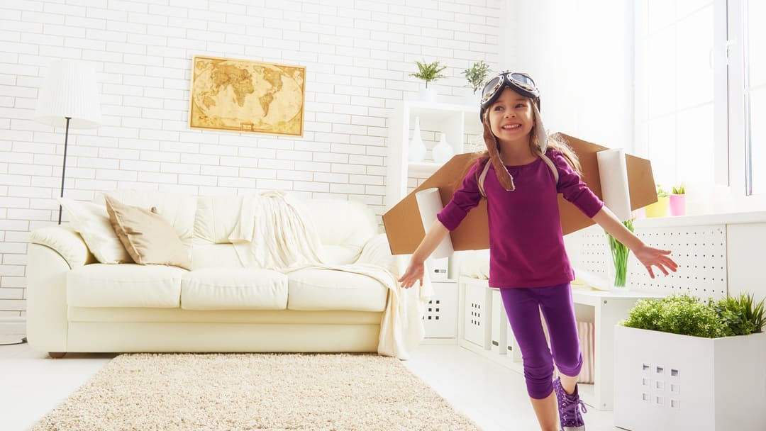 Girl playing planes at home