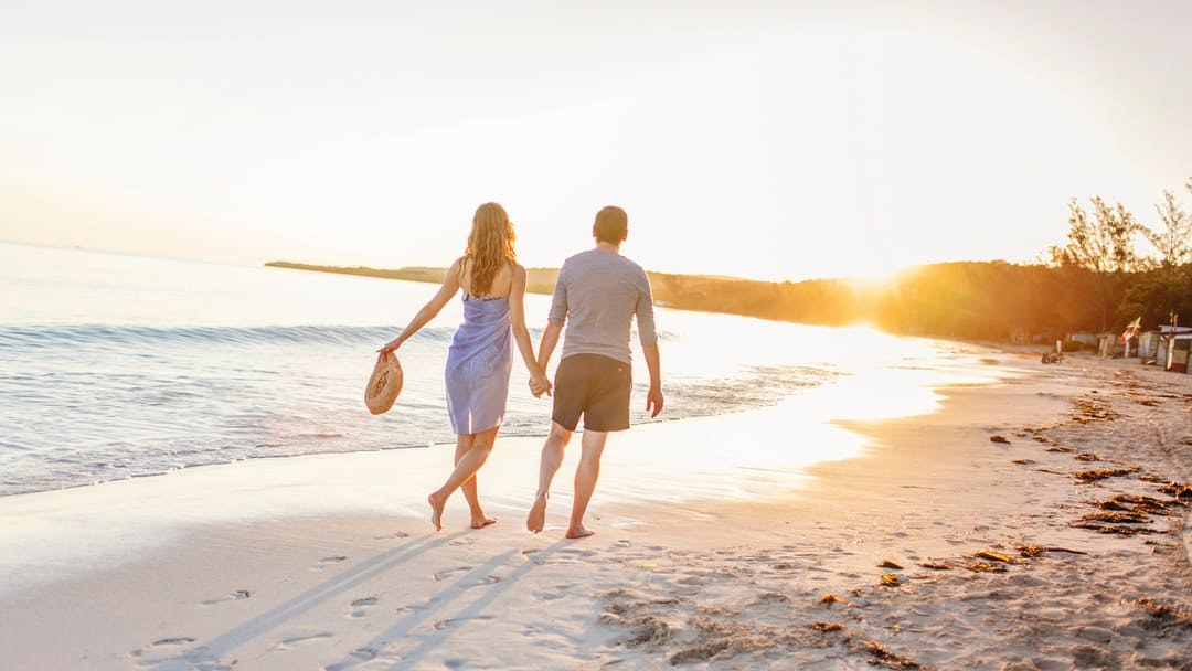 Couple walking along the sunset beach